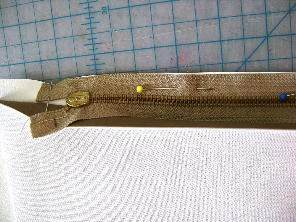 "step 3 - With right sides together, sew the white top vinyl pieces to the chestnut bottom pieces 2 5/8"" from the sides, leaving the center 9"" open for the zipper.  Open the seam, taping down the center seam allowance.  Place the zipper face down on the opening. (The pocket pieces from step 2 are not shown here for better clarity.   Pin the top side of the zipper to the white vinyl and the bottom to the Chestnut vinyl seam allowances."