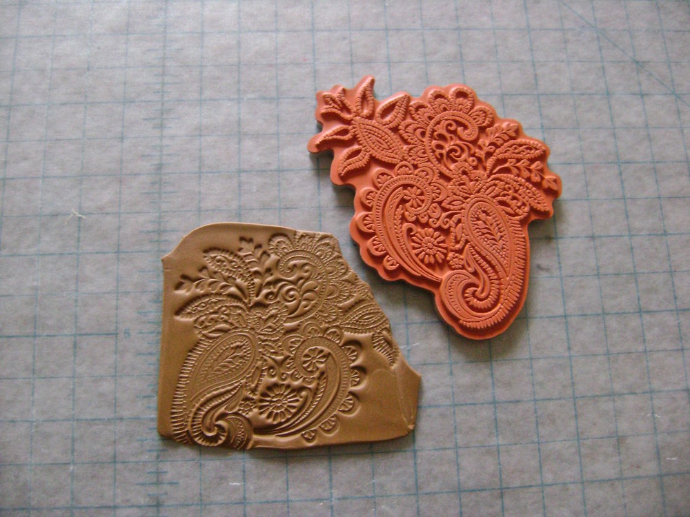 step 21 - To create two clay pieces to cover the clasps, first condition clay.  Impress a floral rubber stamp onto the clay.