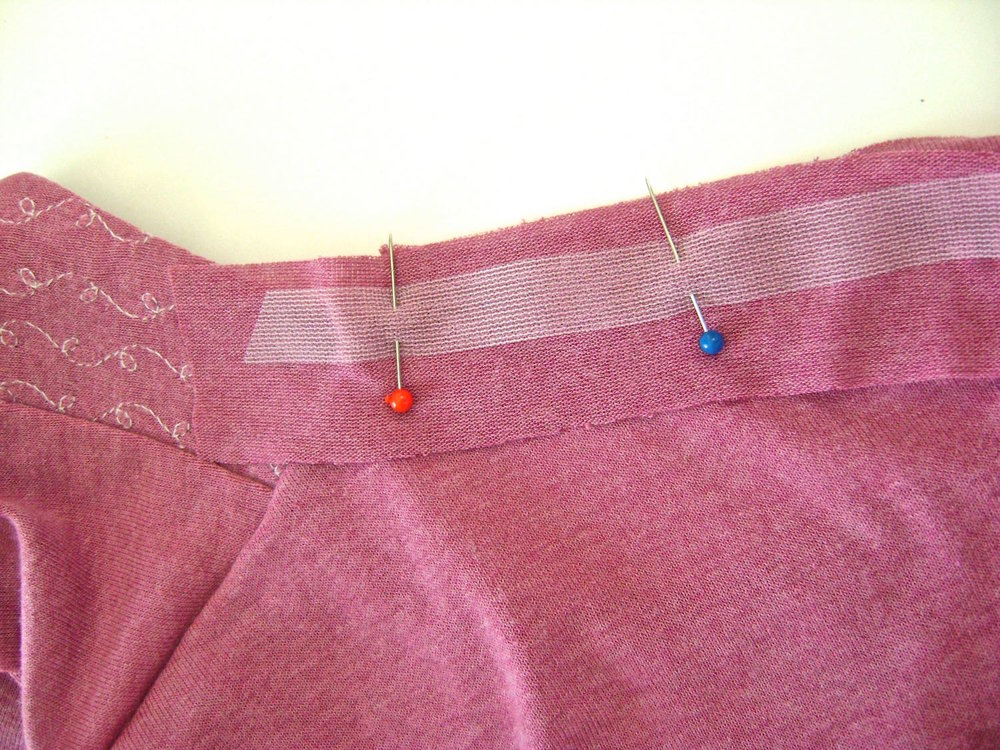 "step 16 - Make a neck band for the shirt back by cutting a strip of fabric 1.25"" by whatever length you need for your size shirt plus two inches.  Pin one raw edge to the neckline along with stay tape. Sew in place from shoulder seam to shoulder seam with one inch of the band extending beyond the shoulder line."