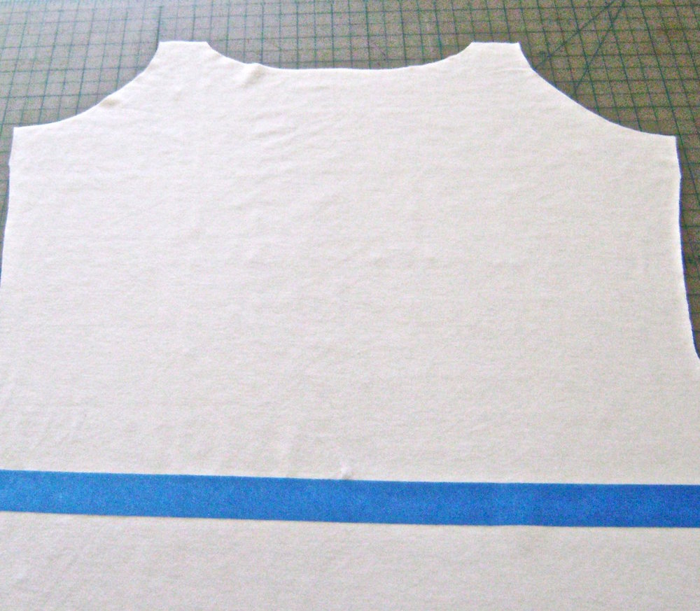 step 2 - Cut out the front and back pieces of your dress. Mark the natural waistline on the fabric pieces with painters tape stretching from one side seam to the other.  This will help you align the stencil straight across the fabric in step 4. Also cut small notches for matching the waistline on both pieces when it's time to sew them together.