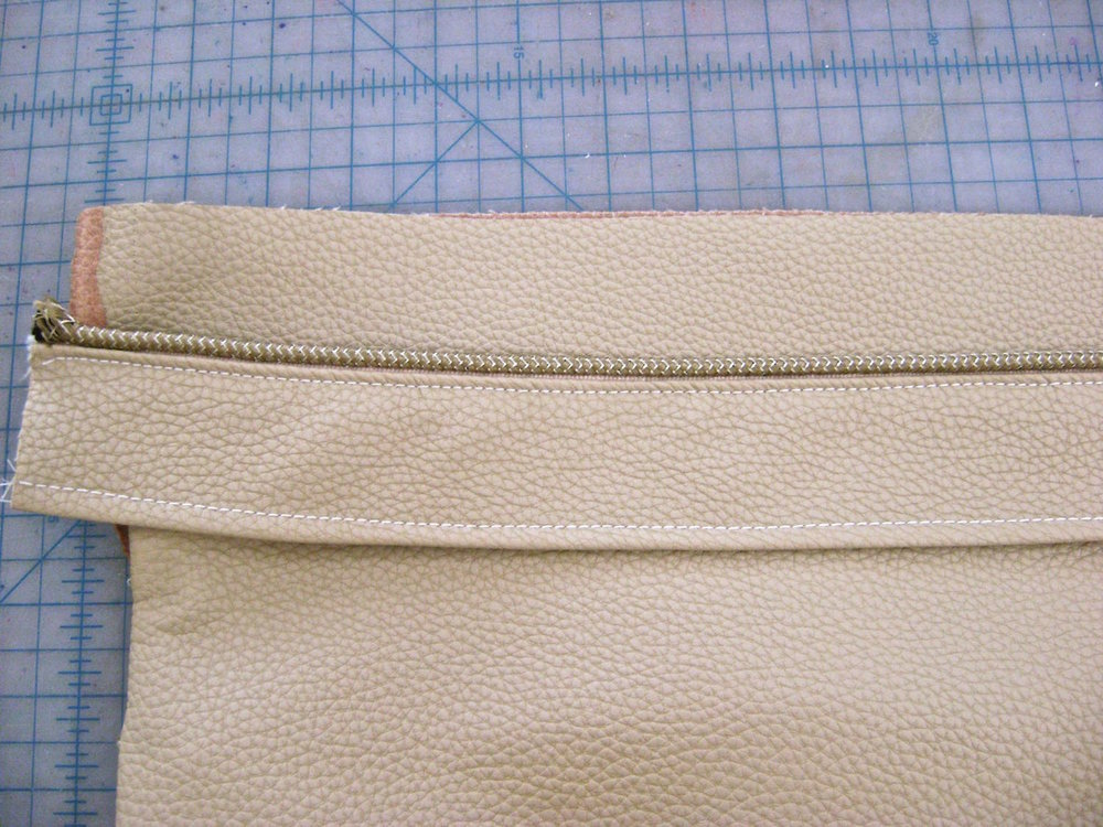 "step 14 - Using a zipper foot, sew a 16"" piece of piping to one edge of the luggage band with right sides together. Stitch the lining right side down over the piping. Sew the other side of the band and lining together using stay tape. Turn the wrong sides together and topstitch .25 from the edges."