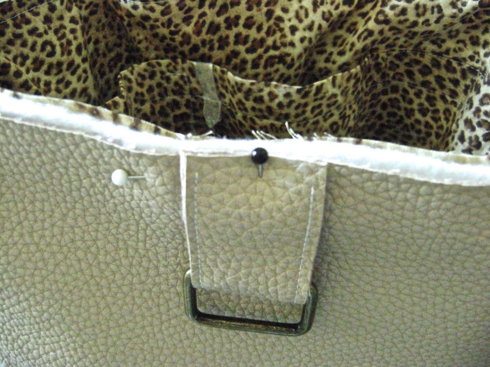 "step 21 - Fold a tab in half and place the metal hardware in the fold. Pin two tabs on the front of the bag and two on the back, each tab 3.75"" from the bag's side seams. Insert the lining/fleece section into the vinyl and sew around the top edge."