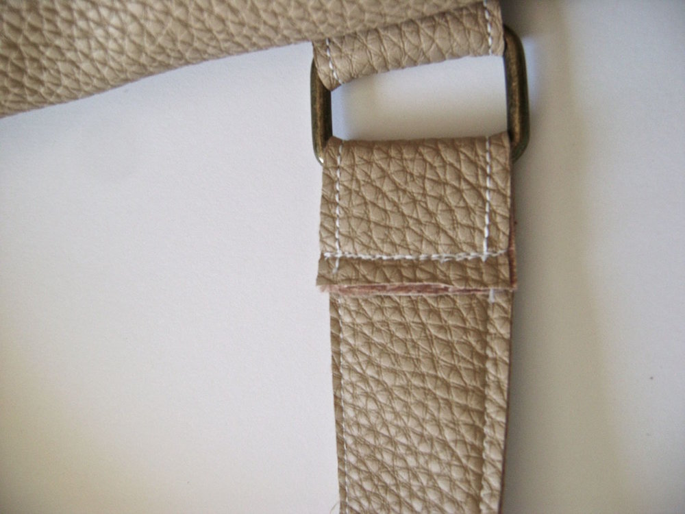 "step 25 - Pull the strap through the metal hardware and fold it at 1.50"". Sew across the strap end two or three times to secure it. Slide the strap covers down to hide the strap stitching."