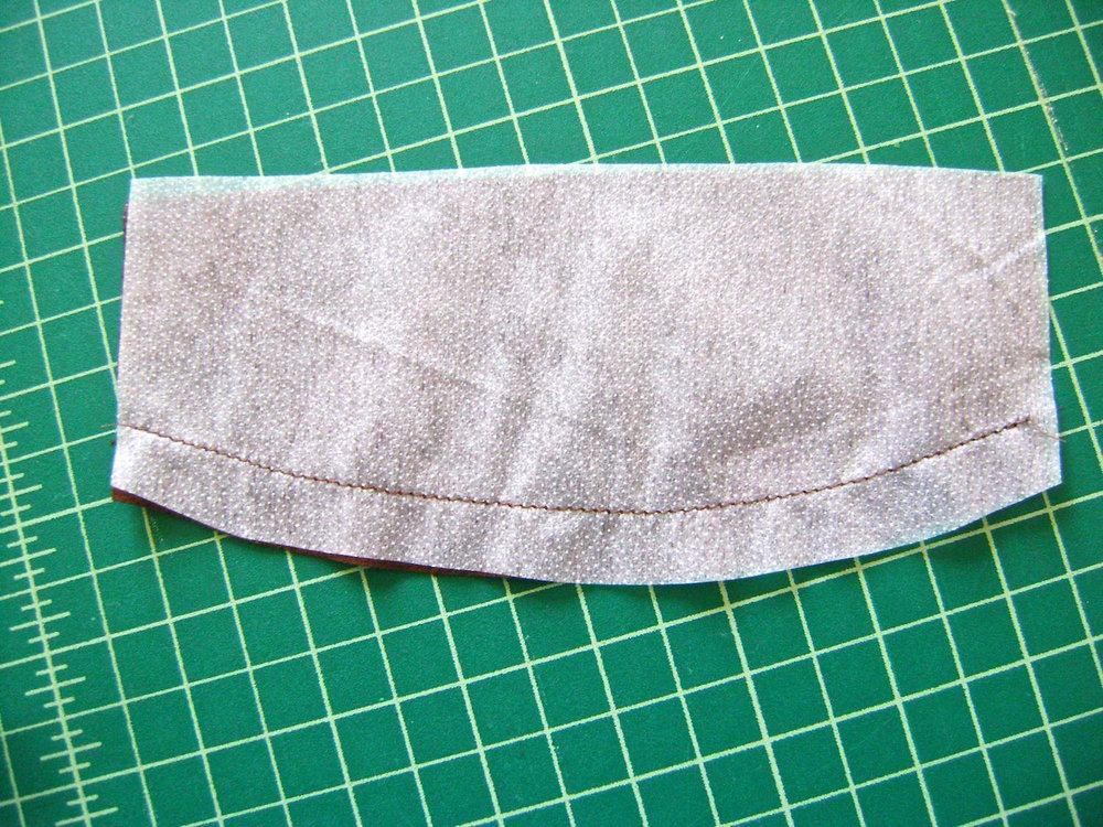 step 2 - Sew interfacing along curved edge of feather cover to fabric with right sides together.