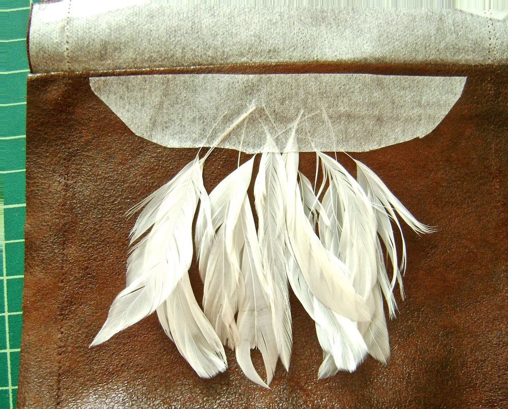 step 5 - Slip feathers under the interfacing centered on the front.  Iron the interfacing to hold the feathers in place temporarily.  Do not iron the feathers.  Check to be sure the cover will hide the quills once sewed in place.  Apply glue to the feather quills to hold them permanently.  Allow the glue to dry.