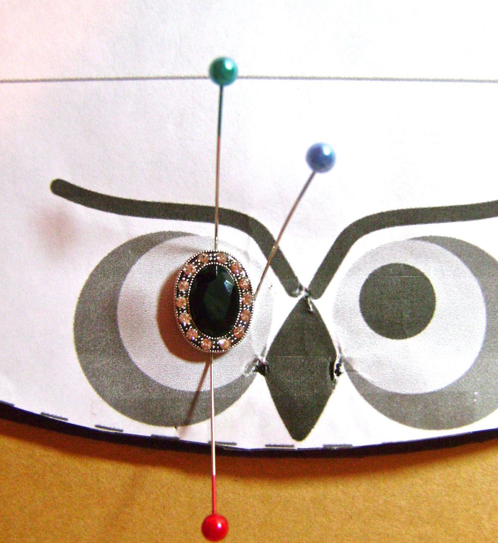 step 12 - Align the pattern piece to the fabric again.  Position the center eye bead and border it with pins to mark its placement.  Remove the pattern, then the pins.