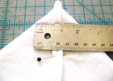 "step 10 - Flatten out the bottom point of the right and left seams in a pyramid shape.  Press with your hands to create temporary creases on angled edges. Place a ruler across the layers, aligning the 1.50"" ruler mark with the side seam stitching.  There should be 1.50"" of fabric to the left and right of center giving you 3' total (not shown).  Make a line against the ruler with a pen or tape.  Machine stitch across the ruled lines to create the flat 3"" bottom of the tote."