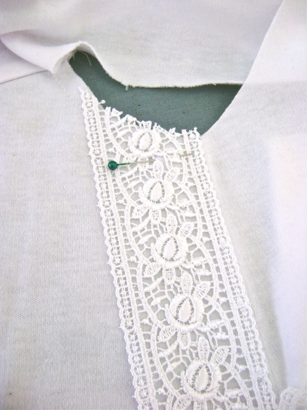 step 13 - Position the lace on the shirt front using the center crease as your guide.  Open out the facing and pin the lace in place.