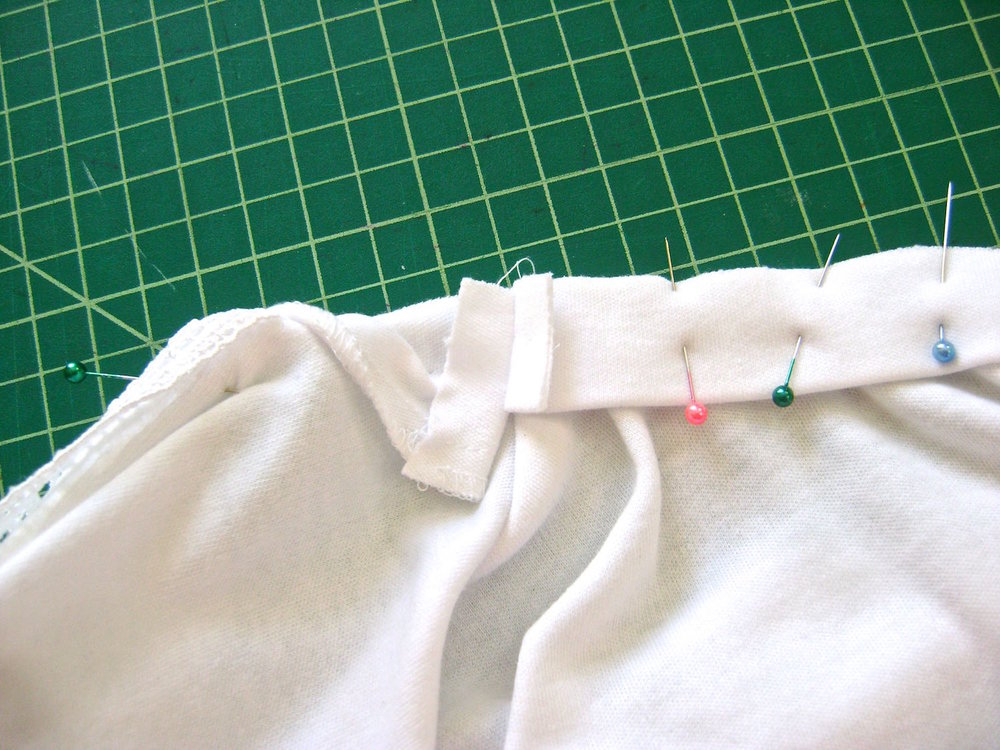 "step 15 - Stay stitch the shirt's back neck edge.  Create a band for the back neck by cutting a strip of fabric the length you need by 2.25"" wide.  Fold the strip in half.  Pin the raw edges to the shirt stretching slightly.  Sew the back band ends to the front facing at the shoulders. Press open the seams."
