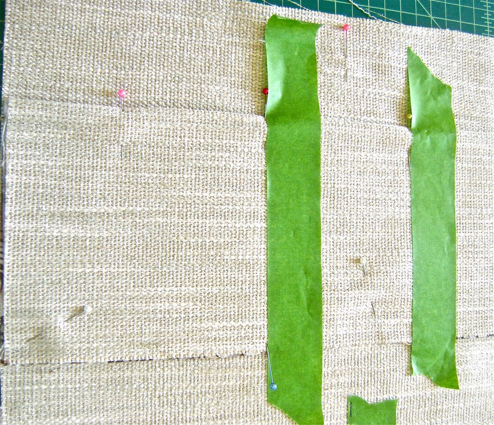 "step 3 - Position the finished edge of the back pocket 2.50"" from the other end of the woven fabric with the pocket edge facing the fabric edge.  Baste in place. Attach masking tape to mark and sew vertical stitching lines for the pockets.  Create sections for storing sunglasses, cell phones, etc.  Design this area so that it suits your needs, making the sections the right size for the items you usually carry."