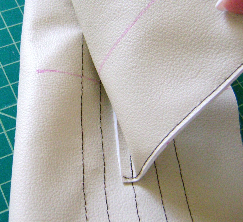 step 8 - With the band open, (not folded in half) align the raw edge of the flap against the first line of stitching at the top inside of the band.  The center of the flap should match the center of the band. Sew the flap to the third line of decorative stitching then trim the allowance.  Turn the flap up and sew another line of stitching to secure it to the top line of the band.  Trim the flap with a thin strip of brown vinyl if desired.