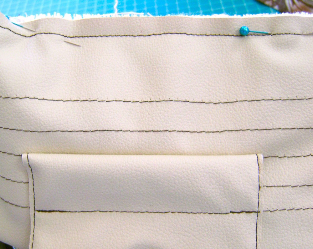 step 13 -  Connect The Band To The Bag  Match up the bottom edges of the band and sew together with a half inch seam.    Match the raw edge of the folded band to the raw edges of the woven fabric and sew together.