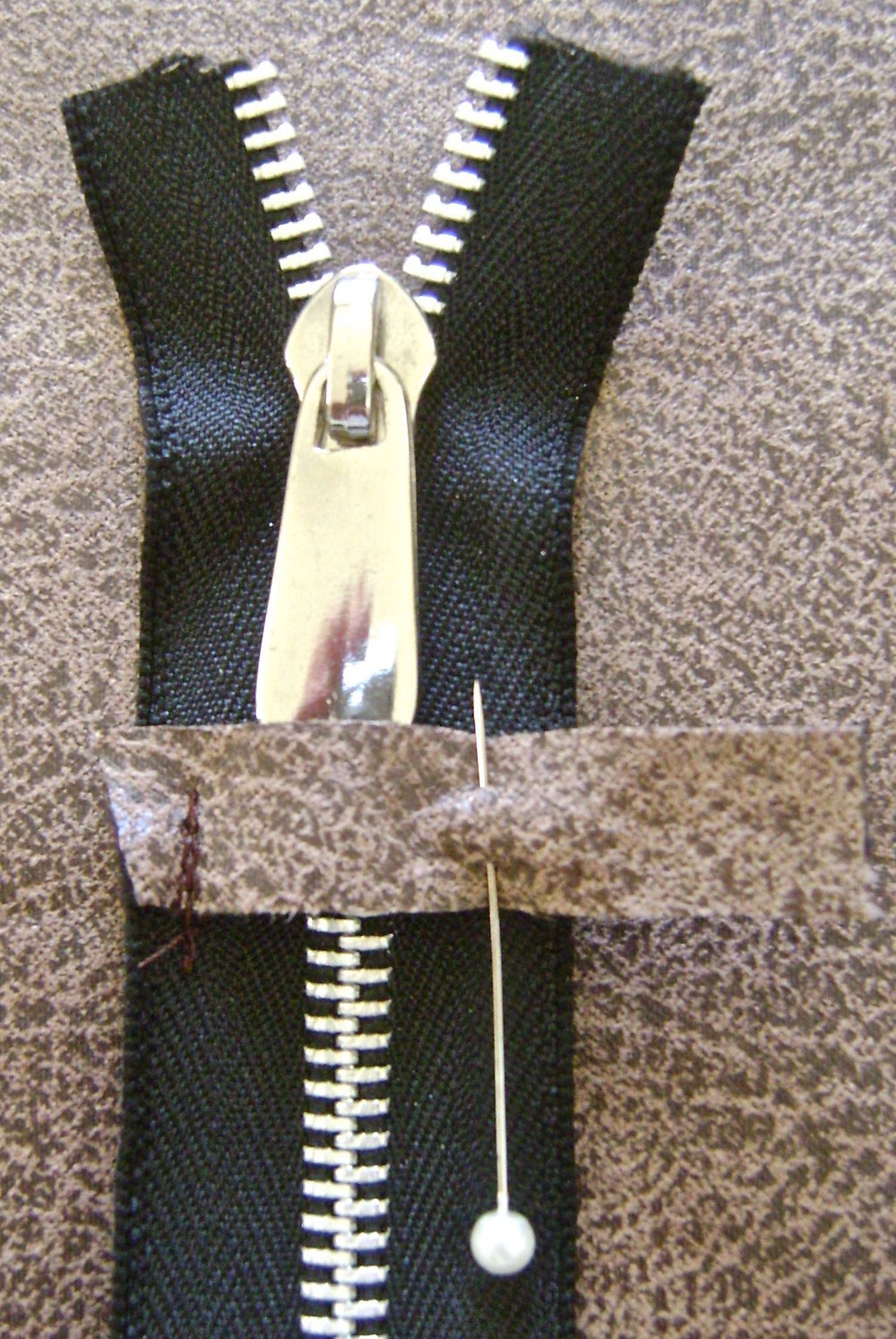 "step 8 - Pin the other stop side to the zipper and slip the decorative pull under the stop.  Move the pull down partially opening to get it on the other side of the stop.  Sew the pinned stop to the zipper.  Trim the zipper ends about .25"" inside the outer edges of the stops."
