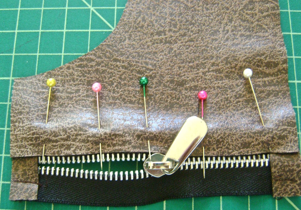 step 10 - Sew the wrong side of left upper pocket to right side of zipper with zipper teeth showing, aligning the stop edges and pocket.  Stitch close to the teeth.  Attach the lower pocket to the zipper making the same alignments.  Sew on the right upper pocket.