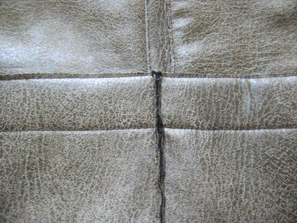 step 16 - The bottom pocket layers over the bottom edge of the zippered pockets.  Use a zipper foot to sew a line of stitching close to the left and right of the bottom pocket center seam.