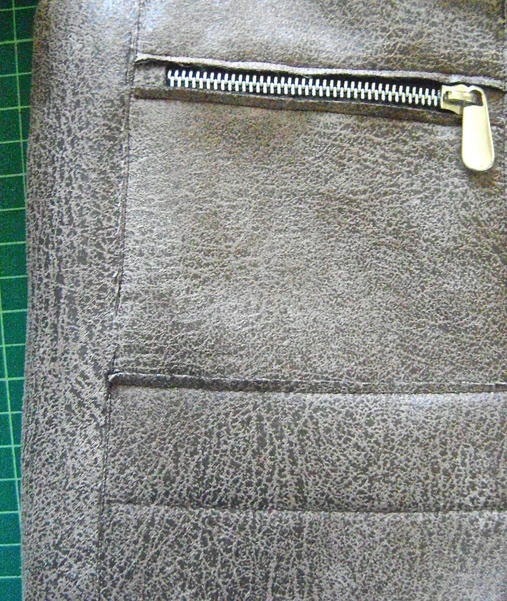 "step 17 - Topstitch a continuous vertical line from the top outside edges of the zippered pockets to the bottom of the lower pockets 1/8"" from the raw edges."