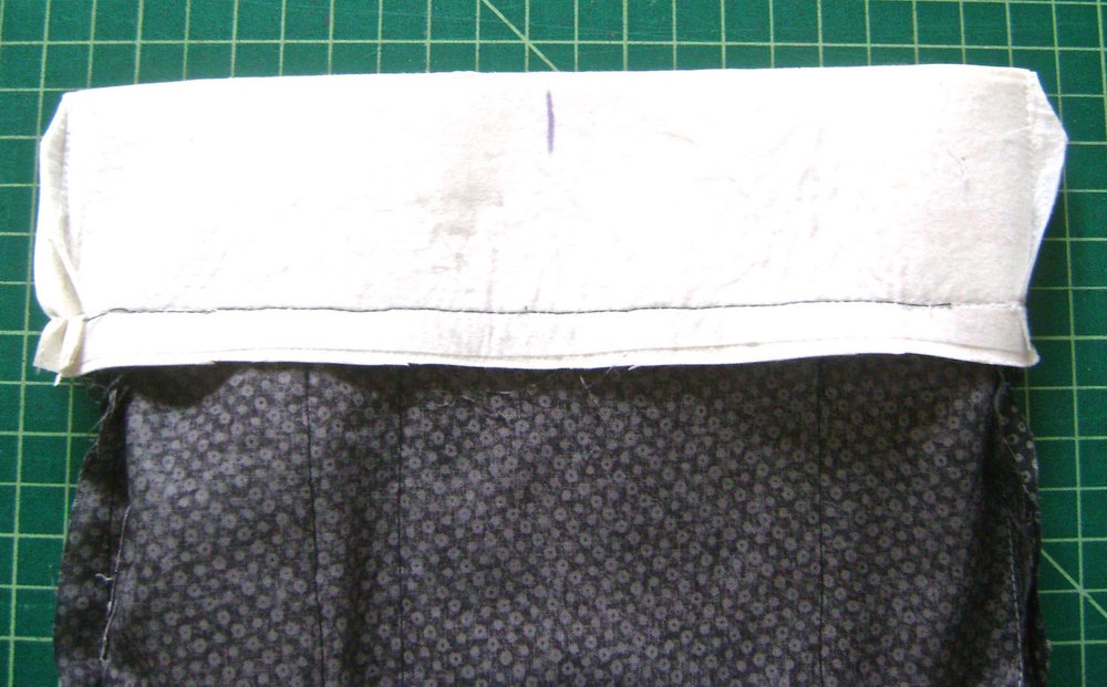 step 11 - With right sides together, stitch the top of the lining to the bottom edge of the purse facing.  On the wrong side mark the center of the facing to help with clasp placement later.