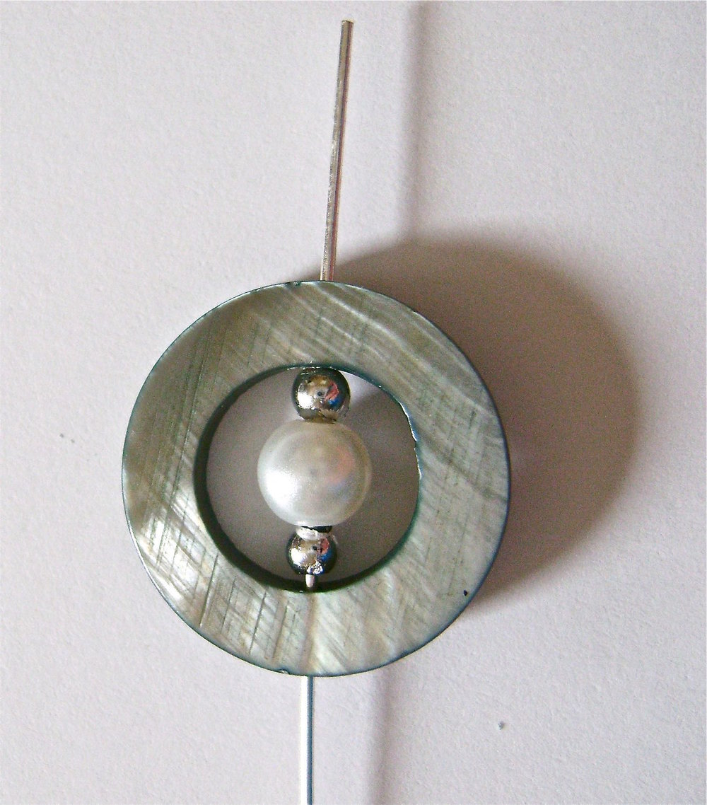 step 2 - Slip on a silver bead, a pearl, and another silver bead.  Move the wire out the hole in the other side of the shell.