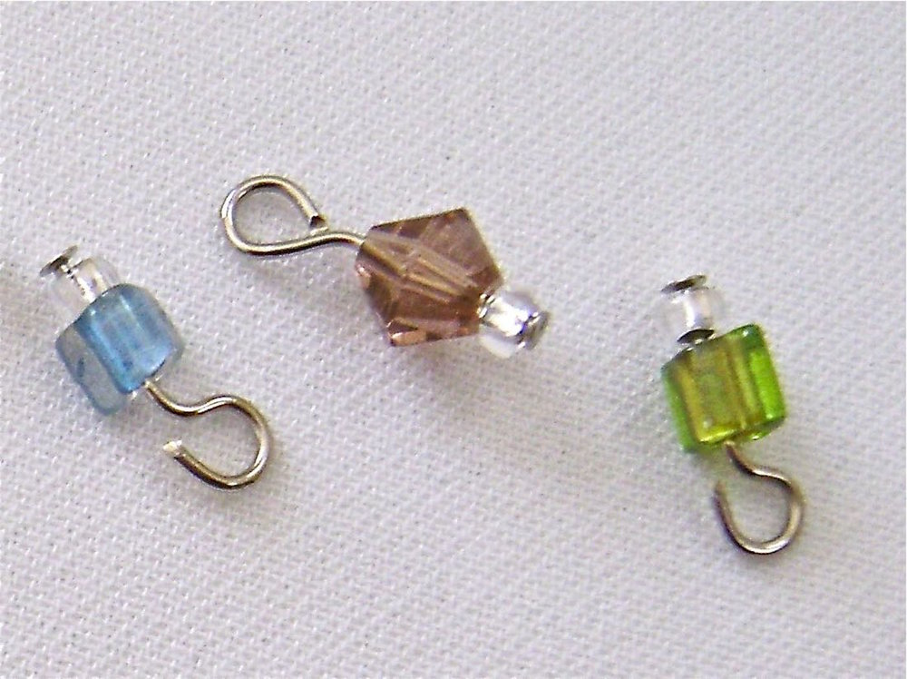 step 2 - Create a set of beads for each link in the chain. (A set = 1 blue, 1 rose, and 1 green bead). Thread a crystal seed bead and a blue cube bead onto a nail head wire. Finish by creating a loop in the wire.  Do not close the loop yet.  Set aside.  If you're unsure of how to make loops/eyes with wire, see the complete instructions in  Jewelry Tools and Techniques .