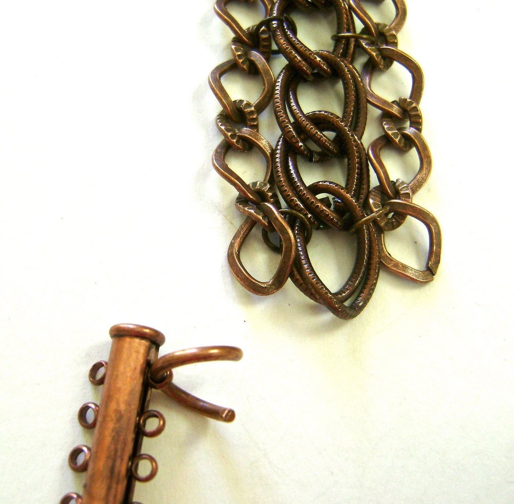 step 2 - Connect the heavy jump ring that came with the chains, to one hole in the clasp.  As an alternative you can also use a link in the chain for the connection.