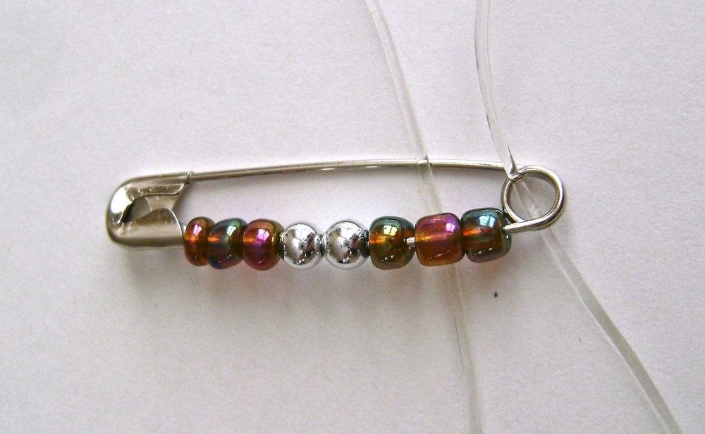 step 1 - Open the pin and slip three colored beads onto it, followed by two 6mm silver beads, then three more colored beads. Close the pin. The multicolored beads come in a bag and are not all perfectly uniform in size, with some being thicker than others. As you add beads to the safety pins the idea is to fill the pin and minimize spacing between beads. As you work, select as many similar sized beads as possible. If you watch the Superbowl while you're working as I did, you may not notice some uneven spacing until you've completed the bracelet.  : )