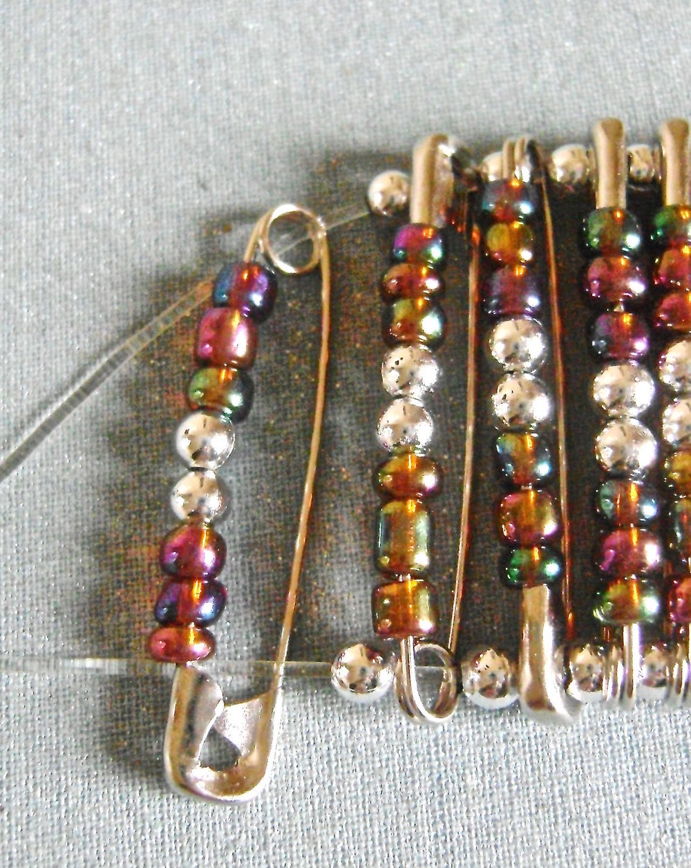 "step 2 - I used 52 pins for this 6.5"" bracelet. Measure your wrist to determine if you need more. Cut two lengths of stretchy cord to measure 8"" or more. Thread the pins onto the cord alternating between pin bottoms and tops with the beads always facing you. Place a 3mm silver bead in between pins. The orientation of the last pin on the cord should be opposite the first pin. After adding the last pin, add a 3mm silver bead to each cord."