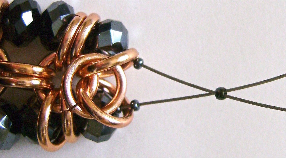 step 8 - Pass the wire through a single bead.  Add two seed beads to each wire.  Put both wire ends into a crimp bead and pull them snugly Be sure to pick up any slack. Crimp the bead to secure the wire.  Trim the excess. The crimp will be hidden inside the copper rings.