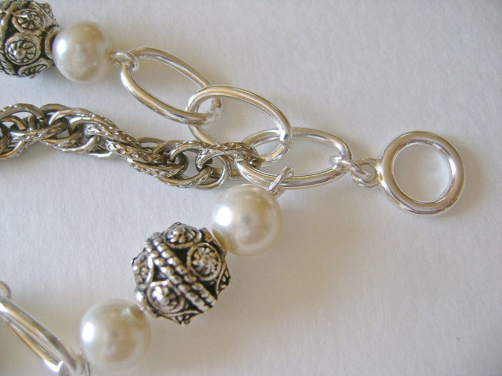 step 6 - Cut a length of ornate chain to match the length of the bracelet. Position the chain between strand one and two. Open the end links and connect them to the silver link connected to the toggle clasp.