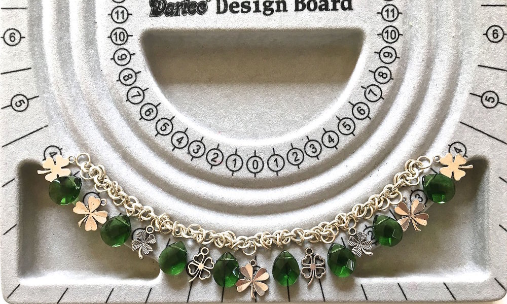 step 2 - Start your placement with a charm in the center of a bead board if you have one. From there work out to one side of the chain alternating beads and charms. Once you know how many pieces are required to complete one side of the chain, you can duplicate it on the other.