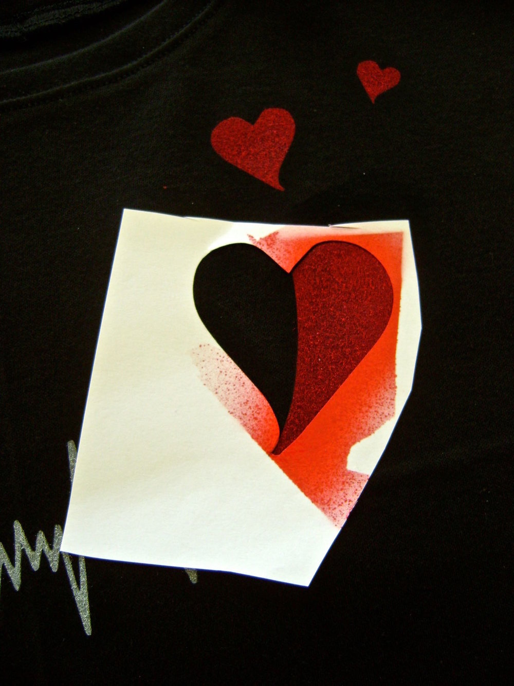 step 7 - Cut out the left side of the large heart on the outer grey line.  Place it back on the shirt in position and align red rhinestones along the border.  Carefully remove the stencil and attach the rhinestones with an iron or rhinestone applicator.