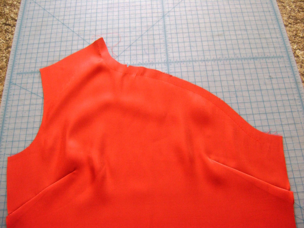"step 2 - Cut out the front of the top and sew a basting stitch on the neckline 5/8"" from the raw edge beginning at the shoulder and ending at the side seam.  Use this stitching as a guide for placing the stencil.  It will help you avoid painting too close to the final stitching line and prevent paint from ending up inside the seam allowance.  With a normal length stitch, create the two darts and press."