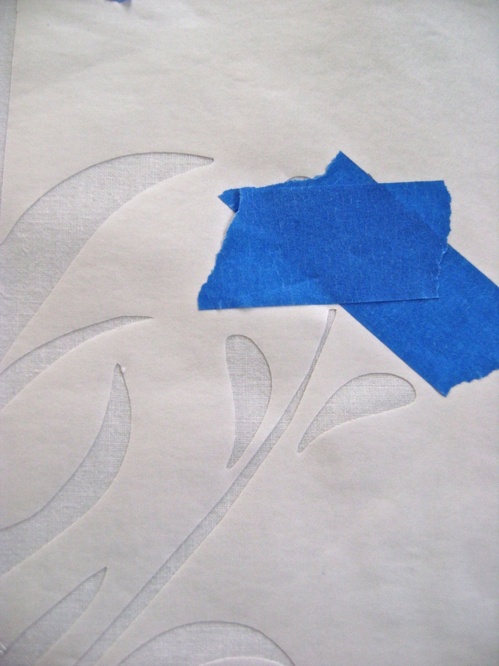 "step 6 - With a dry iron set on ""cotton"", press the Freezer Paper to the white fabric.  Be sure all design edges adhere to the fabric. Place painters tape over the flowers."