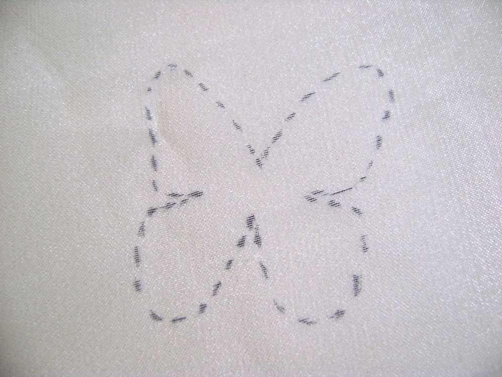 step 14 - Cut two squares of yellow organza large enough to cover one of the butterflies.  Tape only one fabric square to the paper to hold in place while you trace the butterfly with a fine point marker.  Make it elaborate like the stencil or simplify it by drawing fewer curves. Do not use a solid line as the marker will drag on the fabric and distort the shape.  Instead create dots.  Place your dots slightly outside the butterfly border.