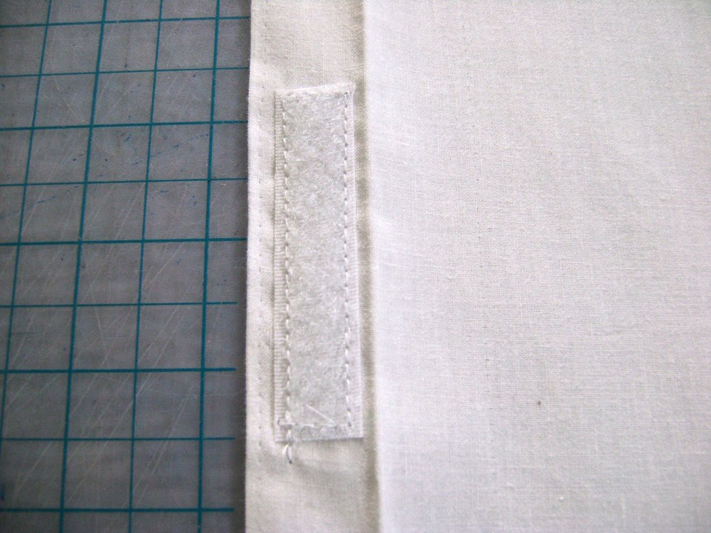 "step 22 - On one piece, sew one half of a 3"" Velcro strip to the center of the hem.  Fold the 1"" hem over again and sew close to the edge the entire length of the fabric.  The piece should now measure 7.75"" x 13.25."
