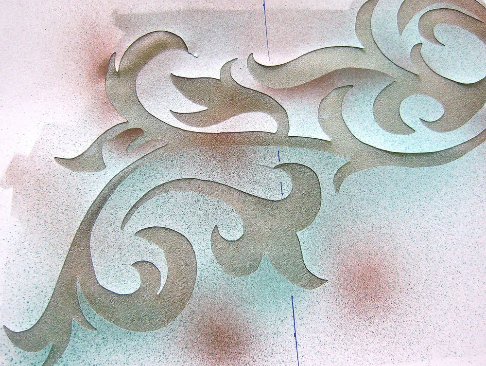 step 7 - Protect the left side of the wrap.  Position the filigree stencils as pictured in the sketch.  Note that the top half of the wrap and bottom mirror each other so the stencils have to be flipped over to be reused.  Spray the stencil with turquoise then dust it lightly in places with brown for accents.  Be sure there is no wet paint on the stencil when you flip it.  Complete all the filigrees in this way.  Let dry completely.