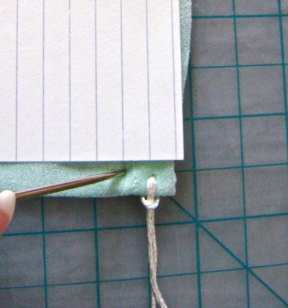 "step 7 - Use the lines on a standard index card to help you space each fringe 1/4"" apart.  Continue adding fringe across the width of the wrap."