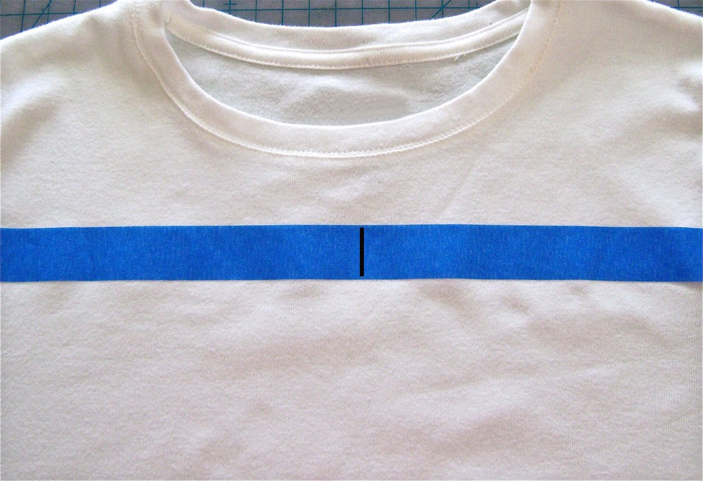 step 1 - Place painters tape across the shirt about thee inches below the neckline to create a straight horizontal line.  Put a vertical mark on the tape to indicate the center front of the shirt.