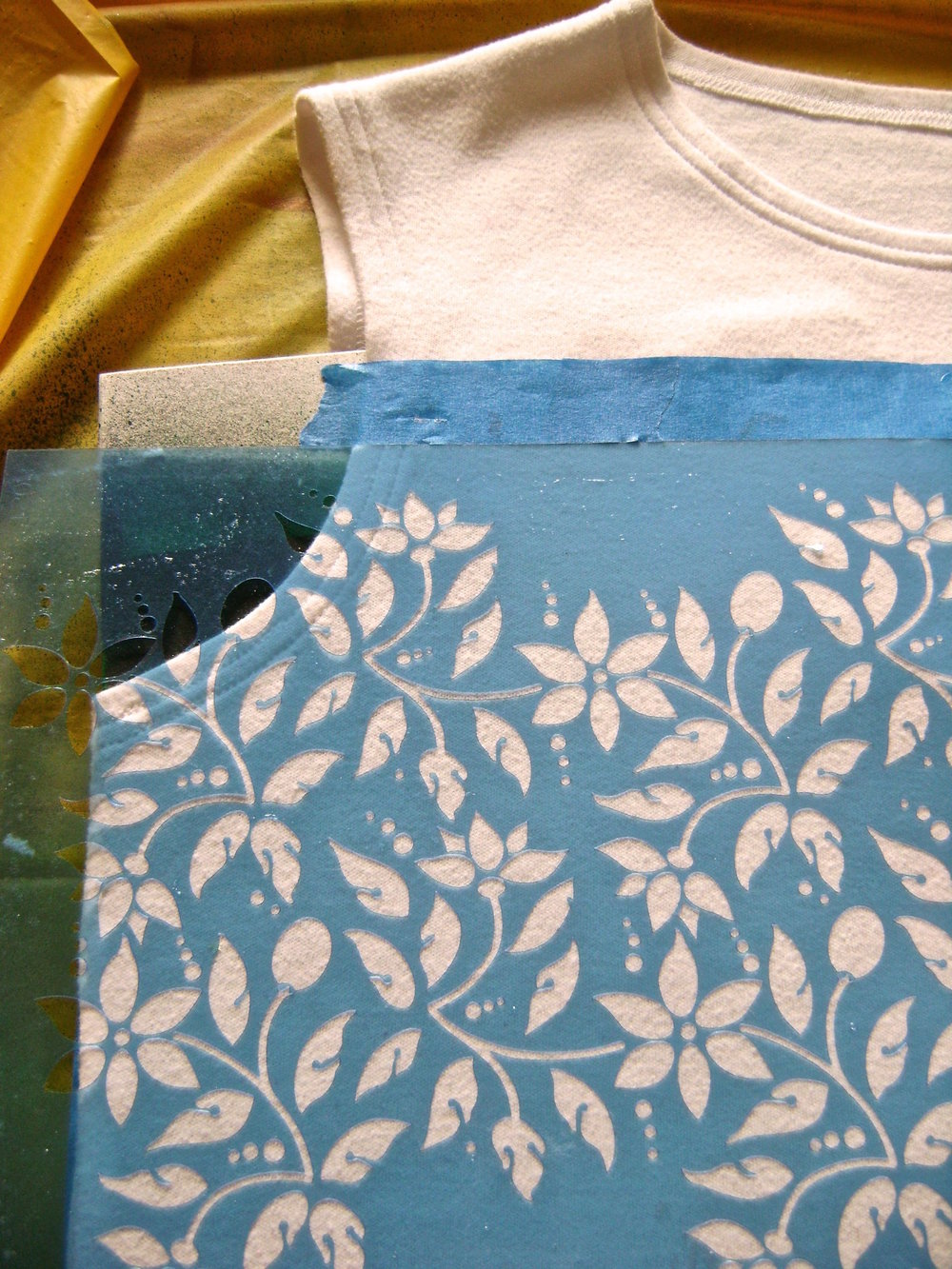 step 4 - Place the stencil on the left side of the shirt with the top edge up against the bottom of the painters tape, and the right edge of the design aligned with the shirt center.  Do not align the right edge of the stencil sheet with the shirt center.  Press down to adhere the stencil to the shirt.   Step 5 - Spray paint the design.