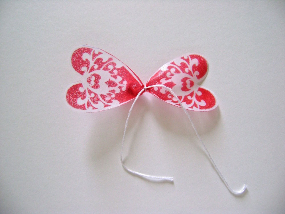 "step 8 - I've used photos of the Valentine flower for these steps because they are clearer.  Tie the center of each petal section with a string and a double knot.  Leave the string tails about 3"" long."