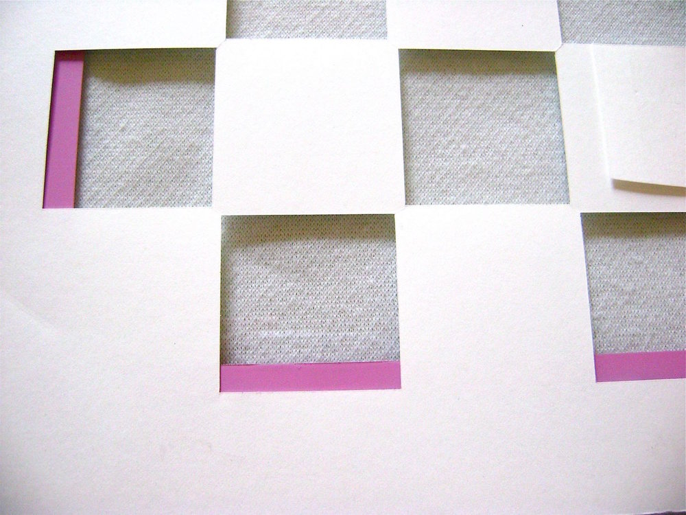 step 9 - Spray adhesive onto the entire back of the board template.  Treat the board template as you did the card stock in step 7, pressing it onto fabric then applying it to the glass.  Be sure that the edges of the template and the glass are aligned.  The pink border will be visible in some squares.