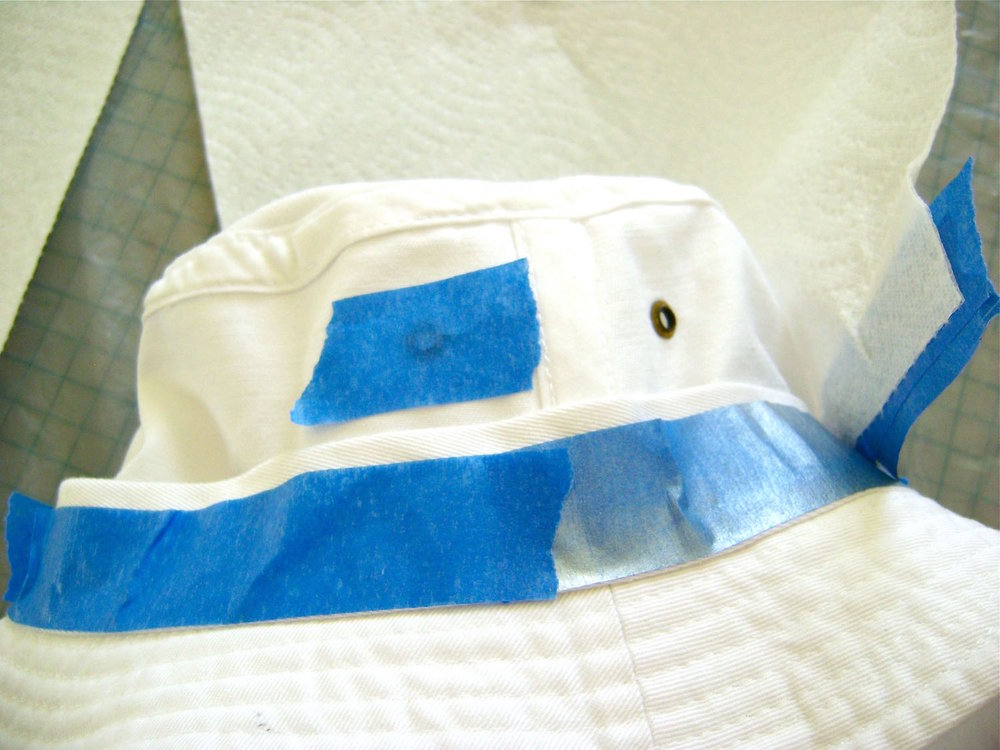 step 4 - Turn the hat inside out and mask off the inside and band with painters tape. Use paper towels to mask most of the fabric.  Put tape over the vent holes too.