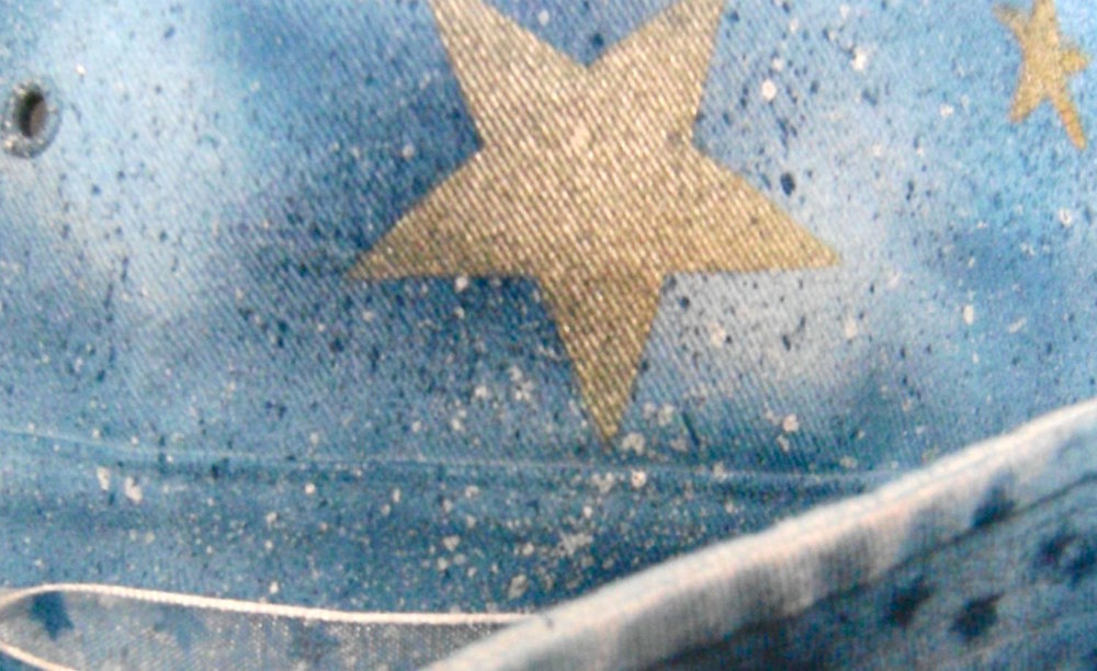 step 12 - Splatter patterns are created using a toothbrush dipped alternately in white and dark blue paint.  Tap the paint-dipped toothbrush on the container to remove excess paint and avoid big splotches on the hat.  With a gloved finger, flick the bristles of the toothbrush near the hat's surface to create tiny splatters.