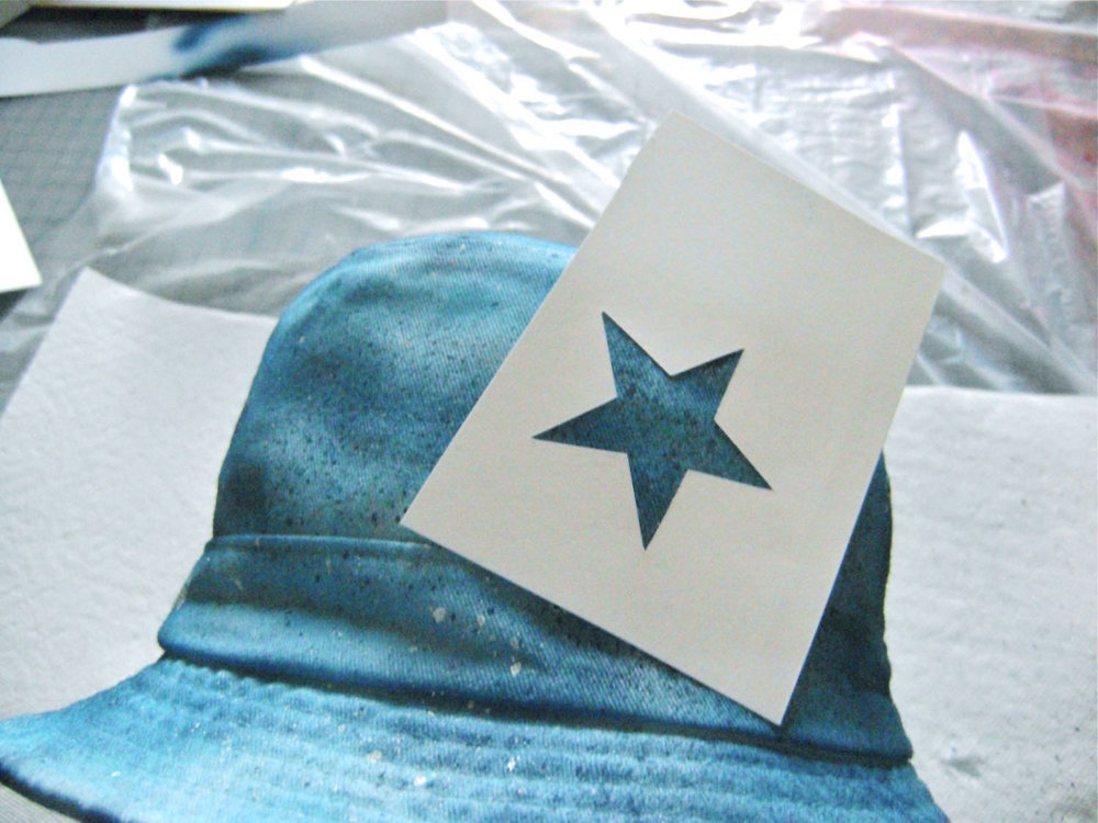 step 13 - Spray the back of the star stencils with repositionable stencil spray and place them on the hat.  Spray with brass paint.
