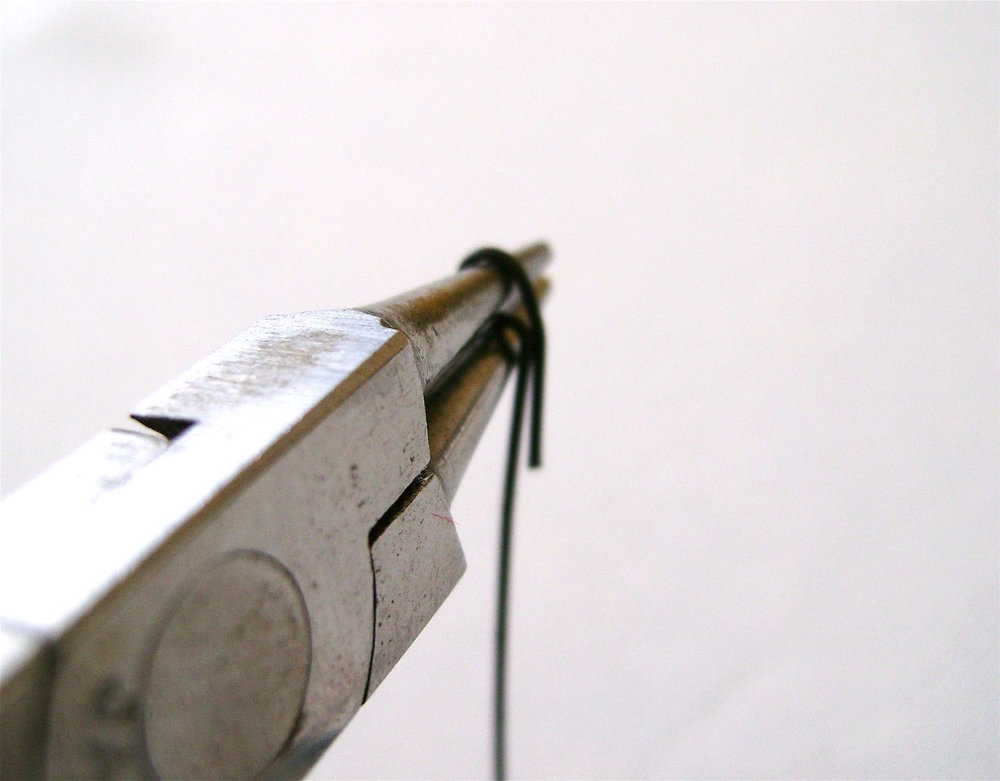 step 15 - Bend the wire down flat against the pliers.