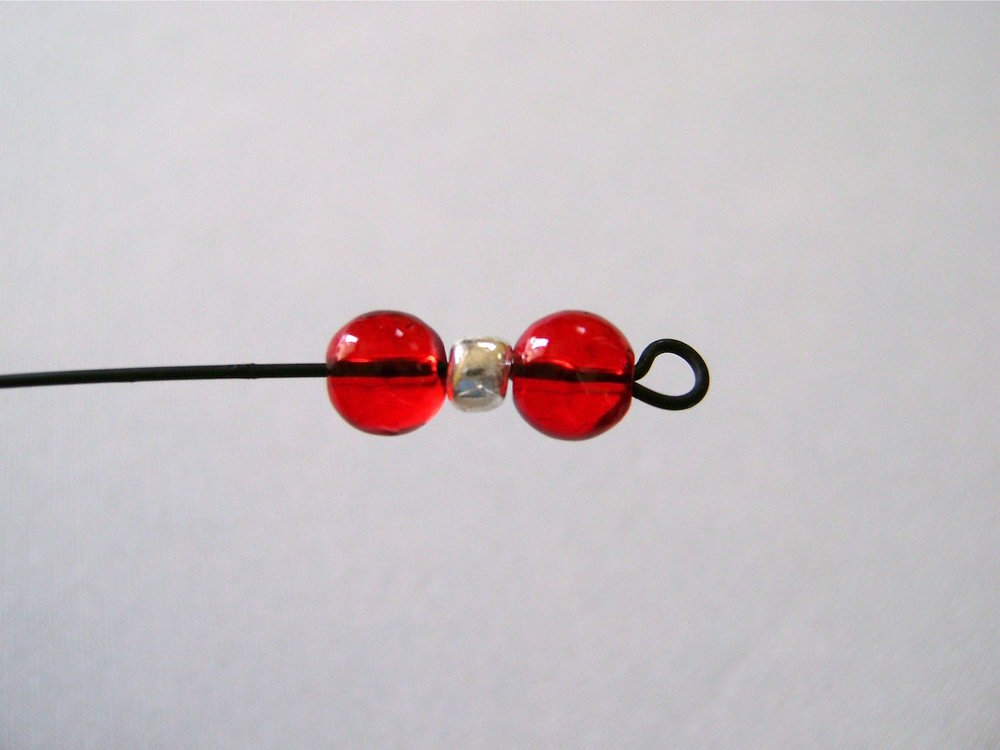 step 18 - Put a red, silver, and another red bead onto the wire.