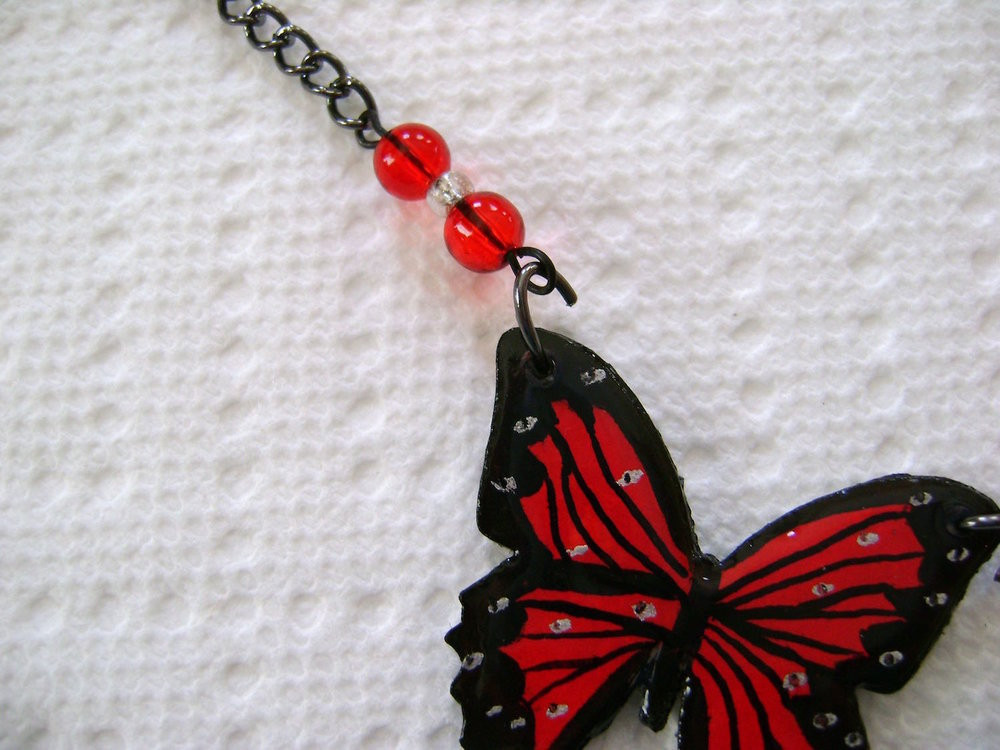 step 22 - Open a jump ring by holding one end stationary and pushing the other end away from you.  Place the jump ring into the hole in the butterfly and into the closed loop of the bead section.  Close the ring by holding one end stationary and pulling the other end toward you.  Repeat to attach the second bead section to the butterfly.