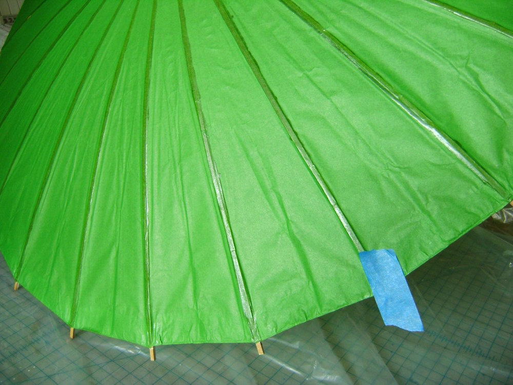 step 1 - Use painters tape to divide the open parasol into four equal sections.