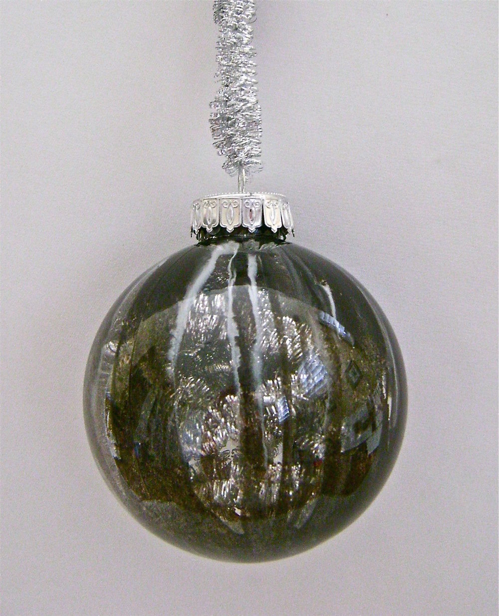 Black Ornament   Apply black, silver and white paint, leaving large gaps between sections.  When the paint is dry, fill the ornament with silver tinsel garland (the kind pictured for the ornament hanger).