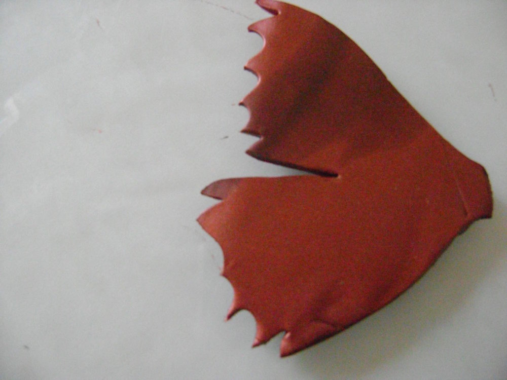 step 6 - Use mini clay cutters with diamond and heart shapes to create the jagged wing edges.