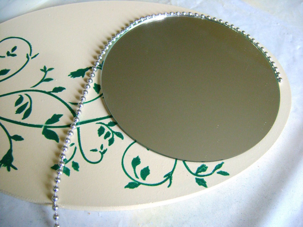 step 13 - Also glue a string of silver beads around the mirror.  Use small dots of the hot glue along the rim, holding each section of beads in place until set.